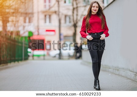 Young woman walking on the street background and smile