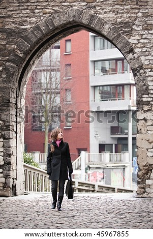 Young woman walking on the streets of old european city