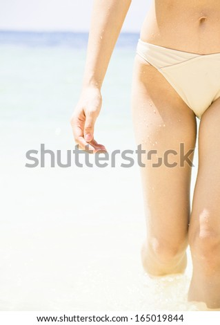 Young woman walking on wet perfect sand