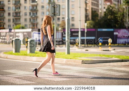Young woman walking street - one foot in sneaker and other in high heel shoe - stock photo