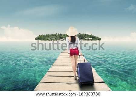 Young woman walking toward island. shot outdoors - stock photo