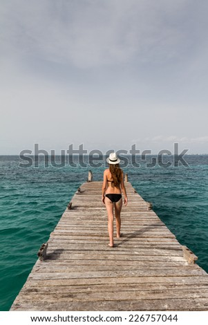 Young woman walking towards the sea at the pier - stock photo