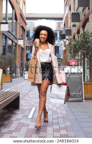 young woman walking with a coffee and shopping bags - stock photo