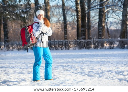 Young woman walking with backpack in winter park, copyspace - stock photo