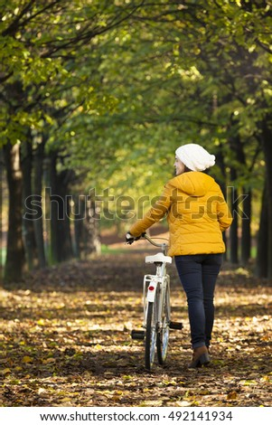 Young woman walking with bicycle in Autumn park