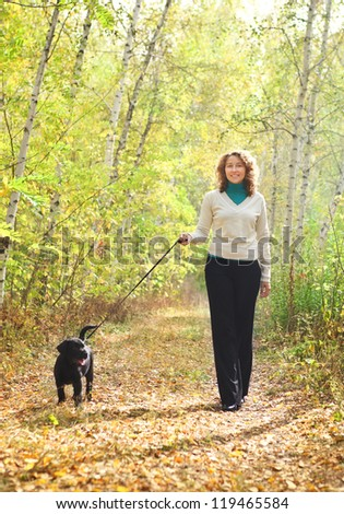 Young woman walking with black labrador retriever puppy in the autumn forest
