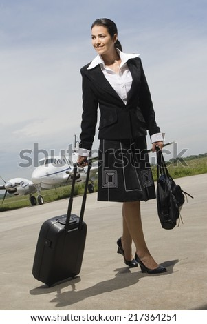 Young woman walking with her luggage at an airport - stock photo