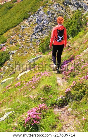 Young woman walks a narrow trail surrounded by pink mountain flowers