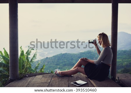 Young woman wanderer is shooting video on her mobile phone, while is sitting against subtropical landscape and sky background with copy space for your advertising text message or promotional content - stock photo