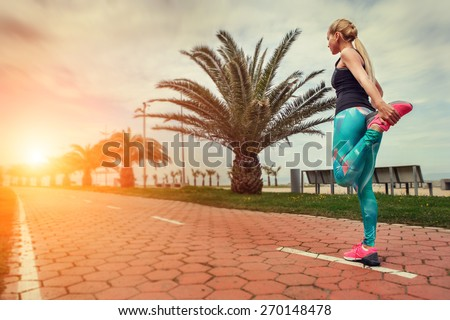 Young woman warm up legs before start jogging - stock photo
