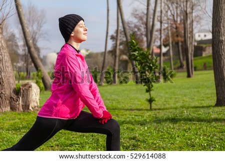 Young woman warming up and stretching the legs before running on a cold winter day in a park.