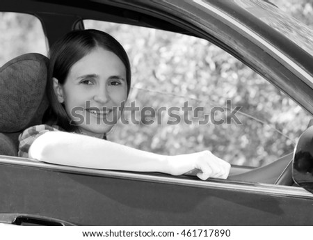 young woman was driving the car.black and white