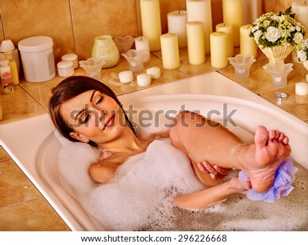 Young woman wash leg and heels in bathtube. - stock photo