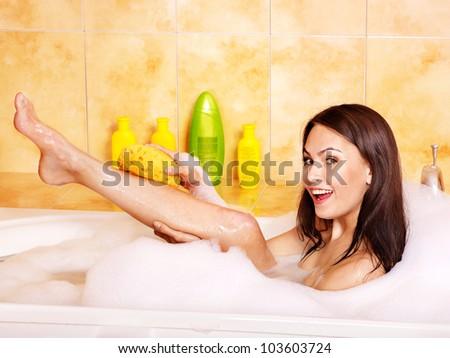 Young woman wash leg in bath tube. - stock photo