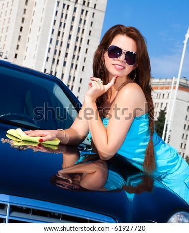 Young woman washing car. Camera angle view. - stock photo