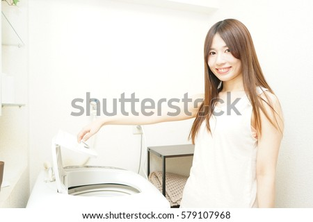 Young woman washing clothes in her room