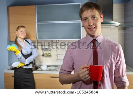 Young woman washing dishes and her boyfriend talking by mobile phone in kitchen
