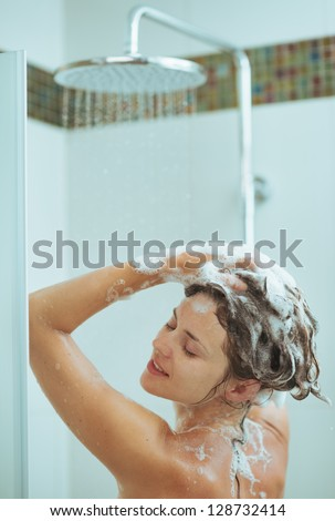 Young woman washing head with shampoo - stock photo