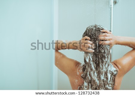 Young woman washing head with shampoo. rear view - stock photo