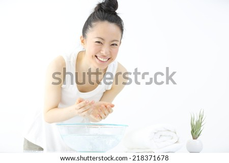 young woman washing her face in bathroom