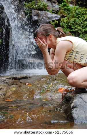Young woman washing her face in mountain stream with waterfall in background