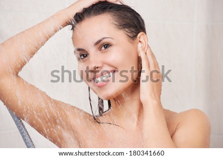 Young woman washing her head in the shower by shampoo - stock photo
