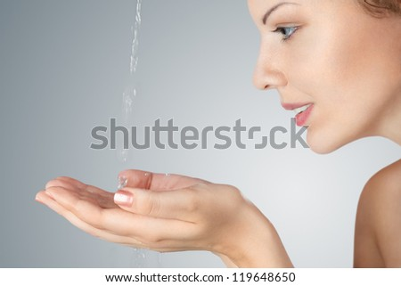 Young woman washing his face and hands with clean water in the morning - stock photo