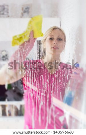 Young woman washing the window glass. - stock photo