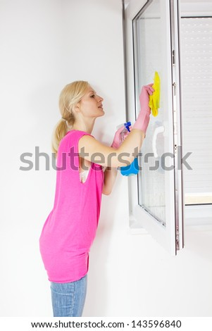 Young woman washing the window glass at living room.