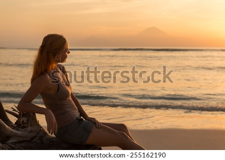 Young woman watching as sun sets over Pacific Ocean - stock photo