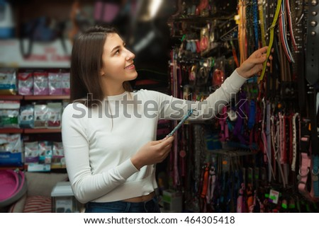 Young woman watching dog harness and smiling in pet store