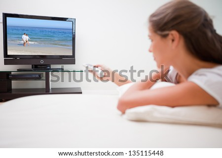 Young woman watching television in the living room - stock photo