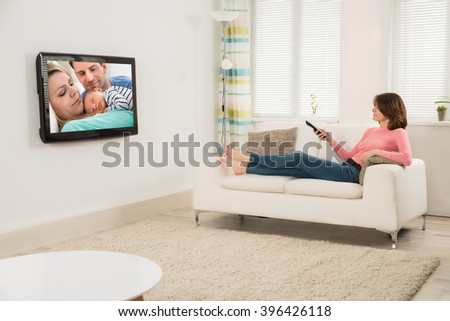 Young Woman Watching Television While Lying On Sofa At Home