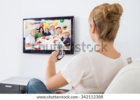 Young woman watching television while sitting on sofa in living room - stock photo