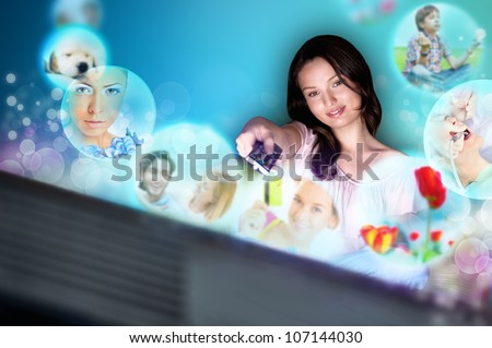 Young woman watching tv at home. Holding remote control and choosing channel. Virtual preview of channels are flying from the screen of her tv