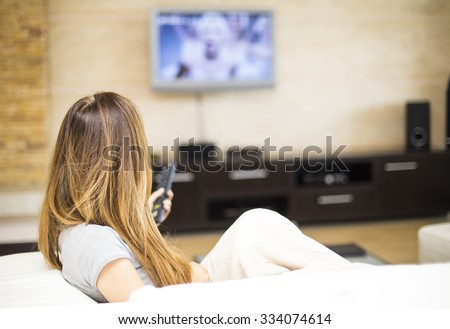 Young woman watching TV in the room - stock photo