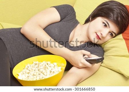 Young woman watching tv on couch  - stock photo