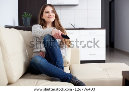 Young woman watching TV on sofa