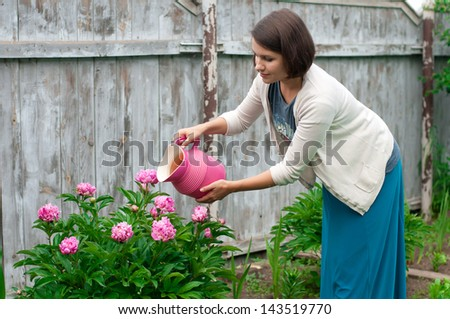 young woman watering flowers in the garden - stock photo