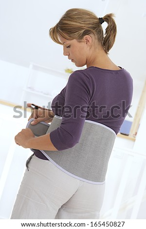young woman wearing a back support belt  -  back view