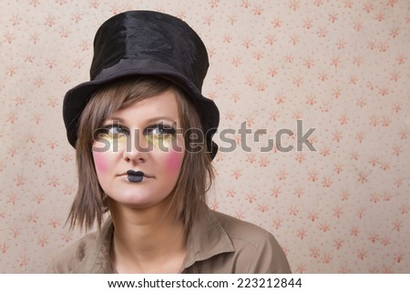 young woman wearing a creative visage and a black top hat - stock photo