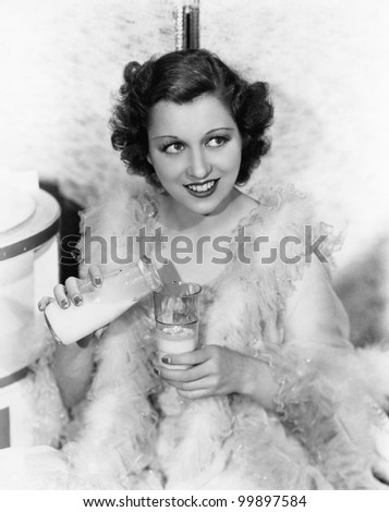 Young woman wearing a feather boa pouring milk into a glass and smiling - stock photo