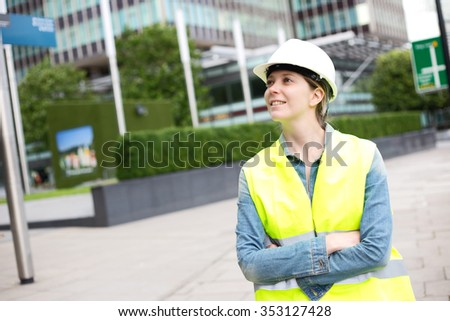 young woman wearing a hard hat and yellow jacket - stock photo
