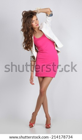 Young woman wearing a pink dress standing - stock photo