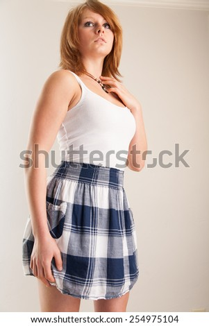 Young woman wearing a plaid skirt and white top - stock photo