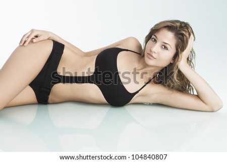 Young woman wearing a swimming costume and laying down on a reflective glass surface.