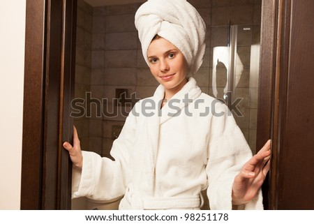 Young woman wearing a white robe in the hotel - stock photo