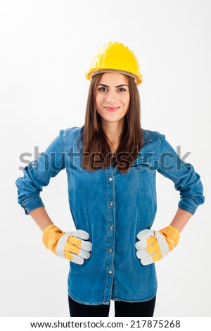 Young woman wearing a yellow hard hat and full protective gear smiling at the camera. Isolated over white in horizontal format. - stock photo