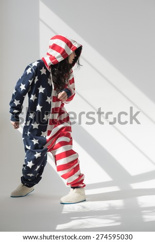 Young woman wearing American Flag pajamas celebrating Independence Day posing in studio - stock photo