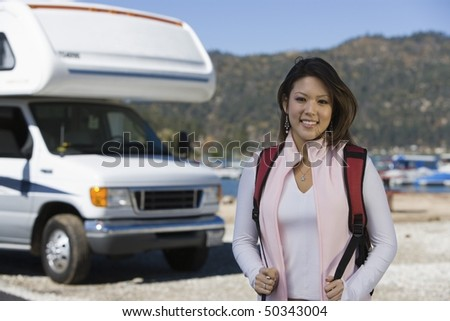Young woman wearing backpack by RV at lake